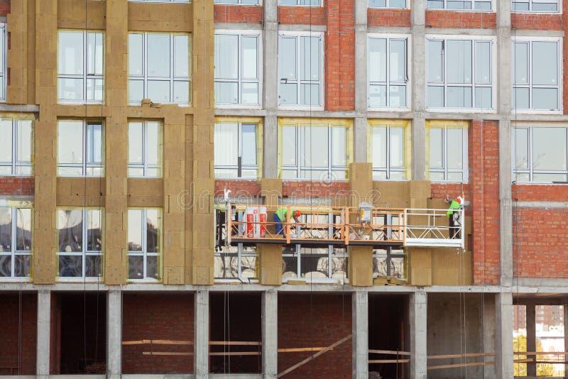 绝缘房子门面的建筑工人 外在墙壁绝缘材料系统或EWIS矿棉节能的 免版税库存照片