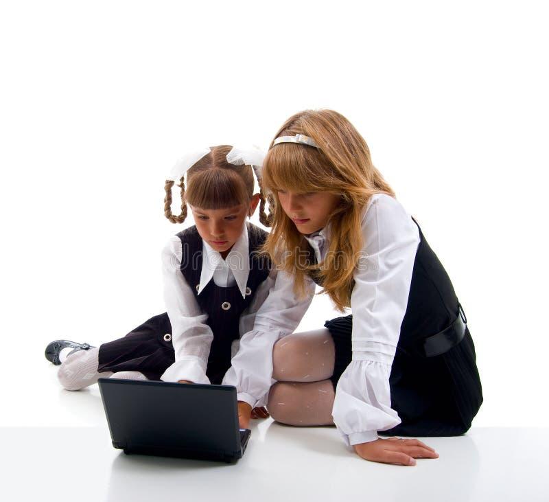 统一膝上型计算机的女小学生 库存图片