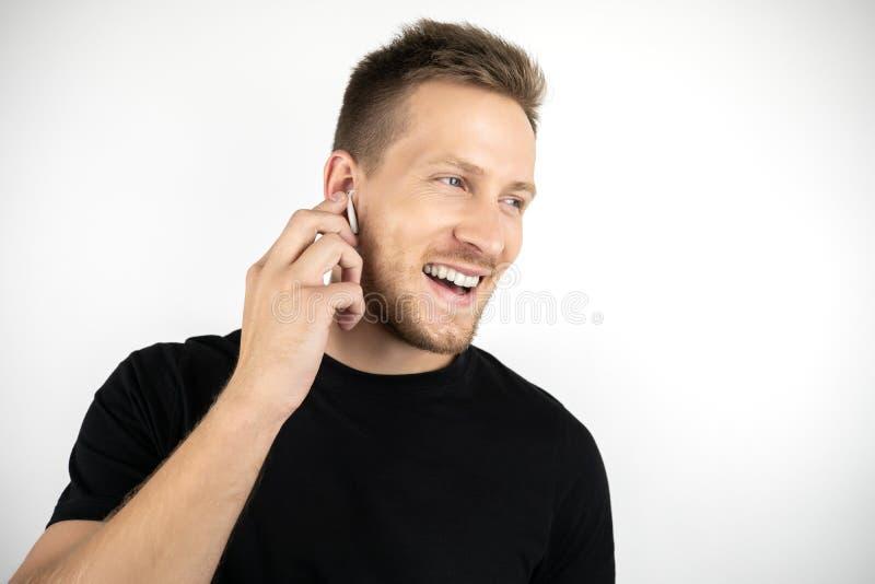 继续下去黑T恤杉的英俊的年轻微笑的人有宜人的通话使用无线耳机  库存图片
