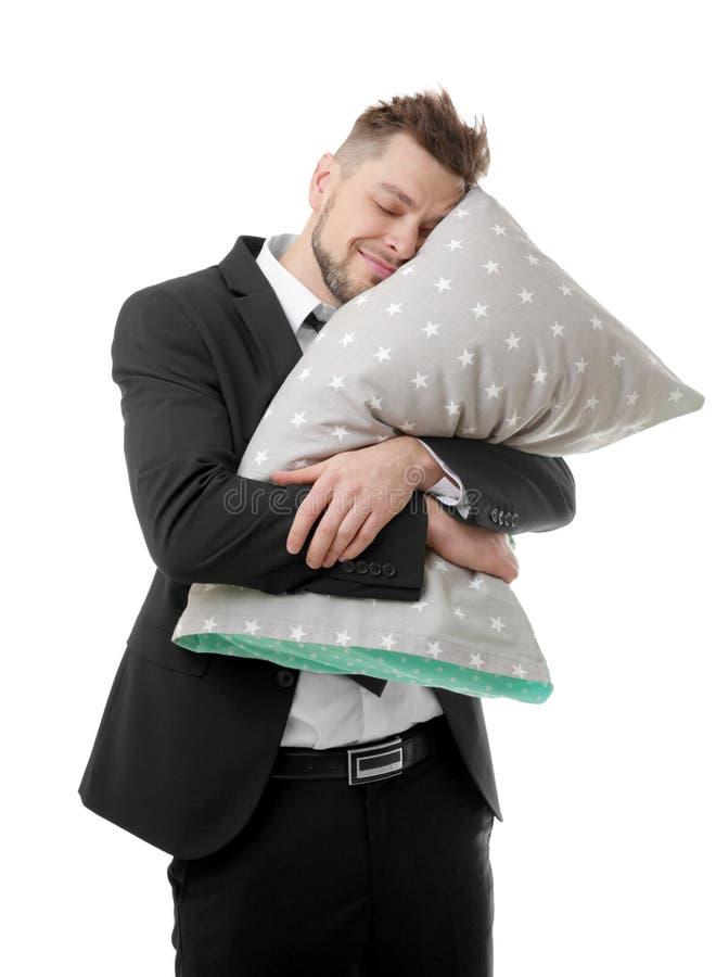 继续年轻的商人拥抱枕头和睡觉,隔绝 库存图片