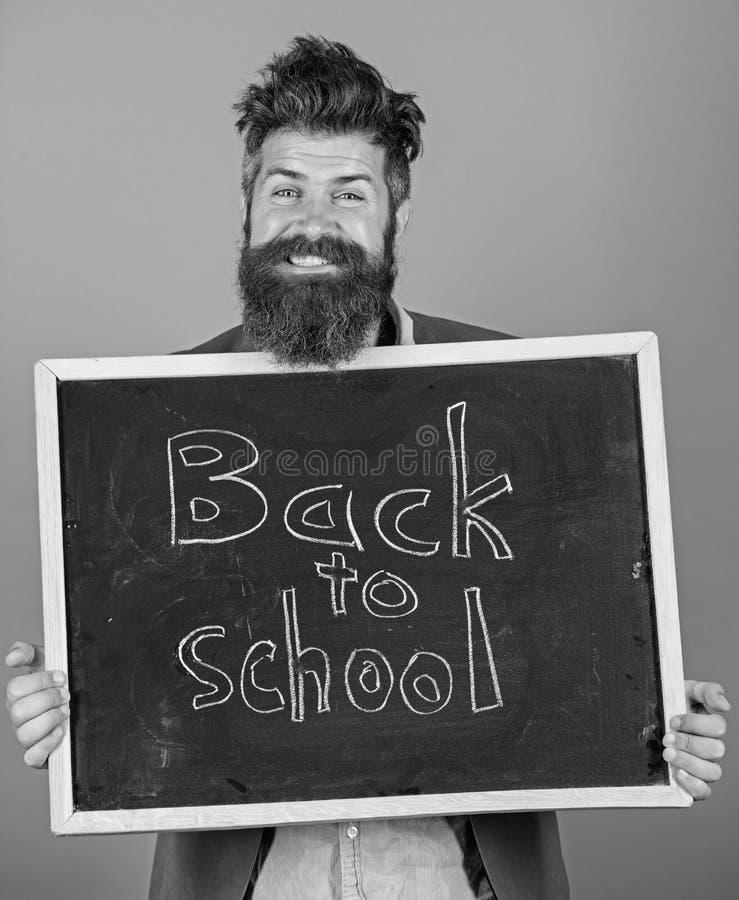 继续您的与我们的教育 老师有胡子的人站立并且拿着有题字的黑板回到学校蓝色 库存图片