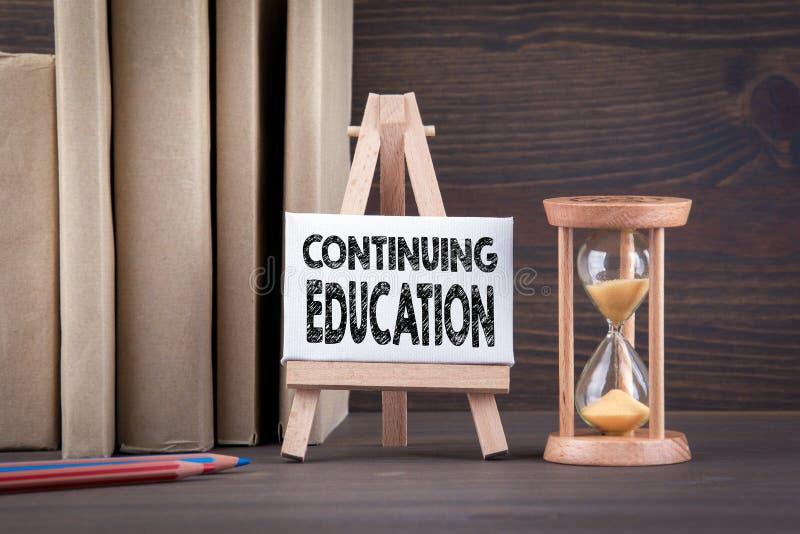 继续教育概念 在木桌上的Sandglass、滴漏或者蛋定时器 免版税库存照片