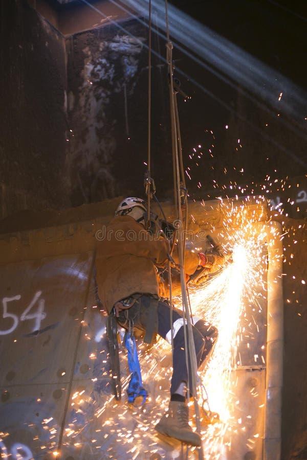 绳索通入建筑工人,佩带的充分的安全身体鞔具,使用电力量研的工具把手的面罩安全 库存图片