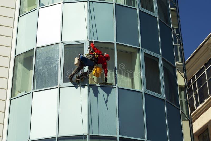 绳索通入技术员洗涤在一座高层建筑物的门面的窗口 库存照片