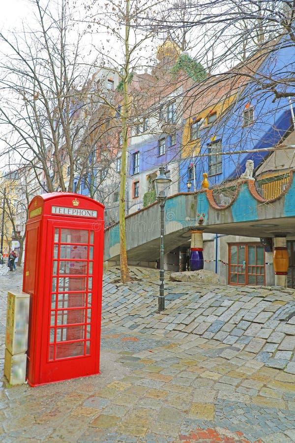 维也纳,奥地利- 2019年1月9日:维也纳街道的红色电话亭有Hundertwasserhaus的 免版税库存照片