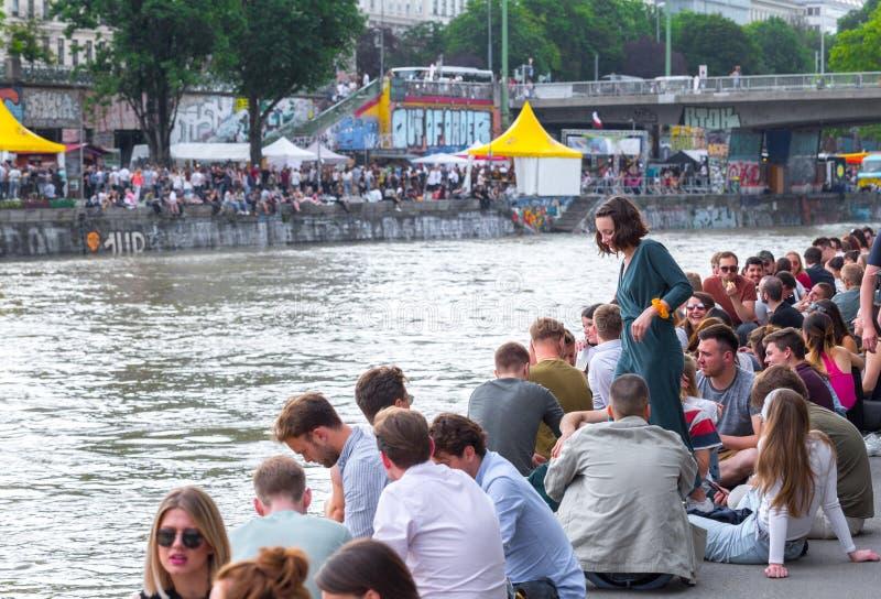 维也纳,奥地利- 5月25:许多人放松与酒精饮料在一个休息日在银行的美好的夏天天气  图库摄影