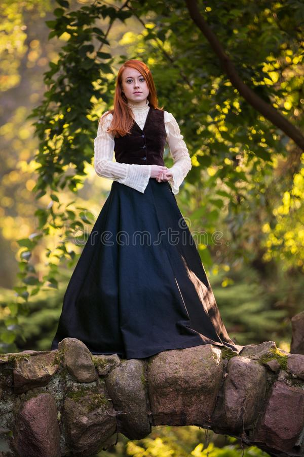 维多利亚女王时代的成套装备的红发妇女 库存照片