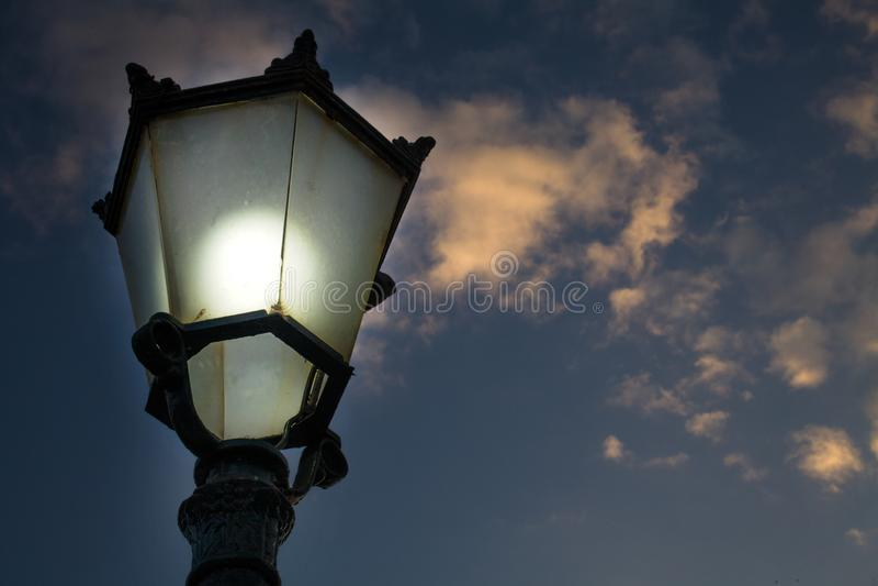 维多利亚女王时代的样式街道灯笼特写镜头射击有熏制的玻璃盖和电灯泡的 室外灯向上看法  免版税库存图片