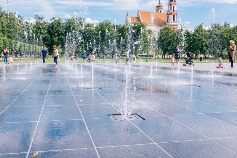 维尔纽斯立陶宛, 2018年7月06日:愉快的孩子获得使用的乐趣在城市给水喷泉在热的夏日在Lukiskiu广场 库存图片