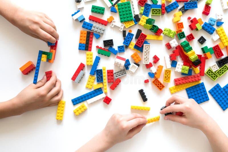 维尔纽斯,立陶宛- 2017年4月 孩子递与五颜六色的lego块的戏剧在白色桌上 库存照片