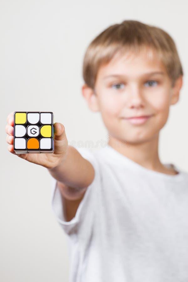 维尔纽斯,立陶宛- 2018年11月21日:小米GiiKER磁性不可思议的立方体玩具在孩子手上 小米汉语 免版税库存照片