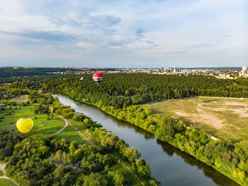 维尔纽斯,立陶宛- 2018年8月12日:飞行在森林的五颜六色的热空气气球包围维尔纽斯市在夏天晚上 库存图片
