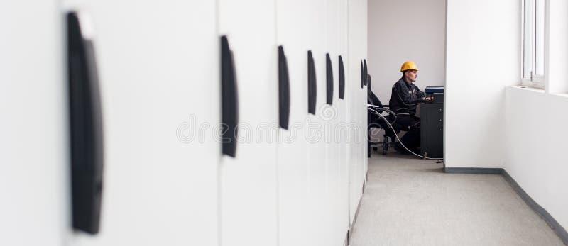 维护工程师检查中转与膝上型计算机的安全系统 图库摄影