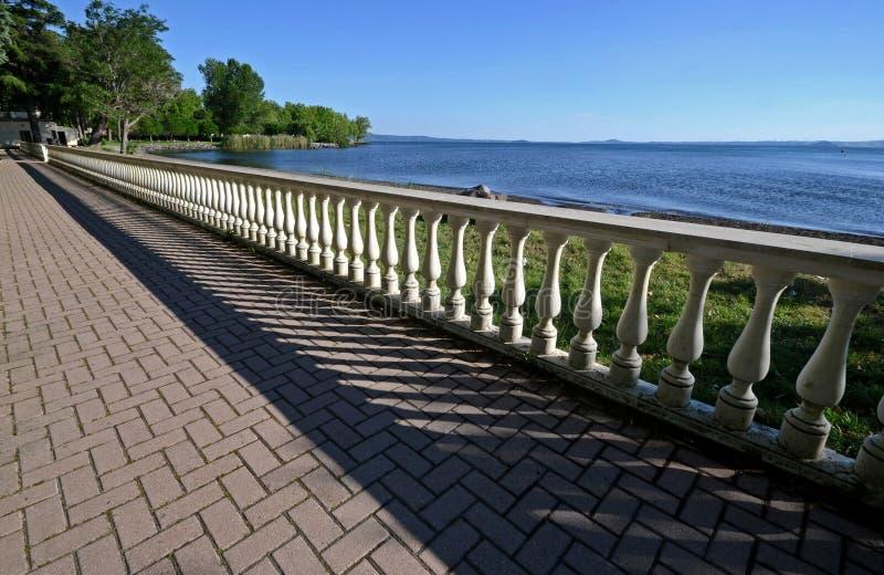 维泰博,意大利,有楼梯栏杆的步行街道沿Bolsena湖的岸,在一春天好日子 库存照片