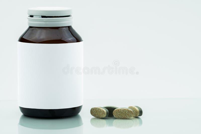 维生素、补充和矿物双倍层数片剂药片和医学琥珀色的玻璃瓶有在白色隔绝的空白的标签的 免版税库存照片