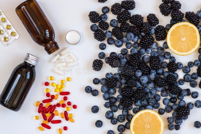维生素和补充从蓝莓和柠檬 配药关心健康视觉 生物健康的活跃补充 免版税图库摄影