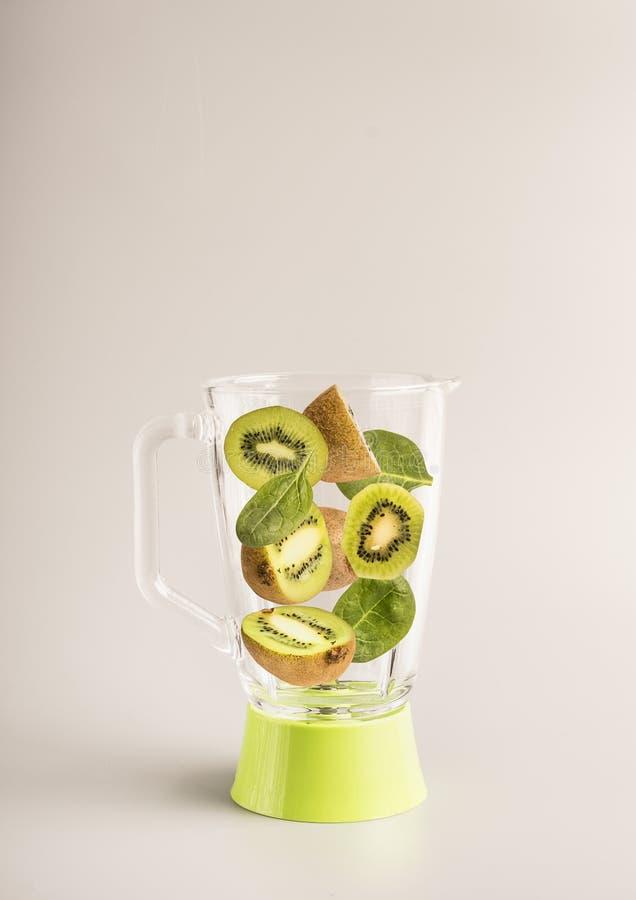 维生素圆滑的人、切的桔子、猕猴桃和菠菜在一台绿色玻璃搅拌器,地方的准备的成份文本的, 库存照片