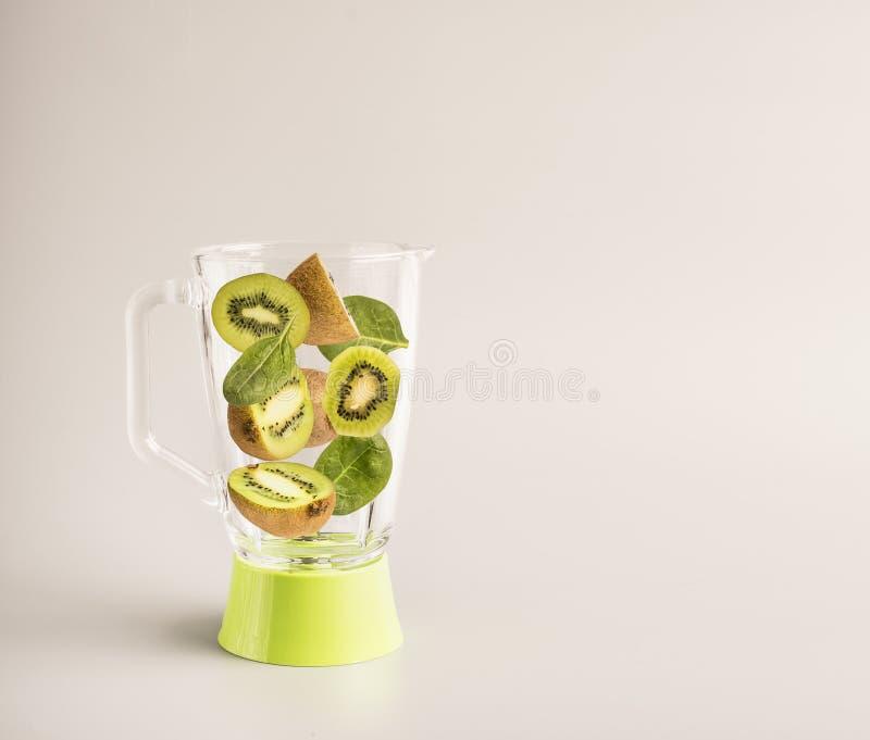 维生素圆滑的人、切的桔子、猕猴桃和菠菜在一台绿色玻璃搅拌器,地方的准备的成份文本的, b 库存照片