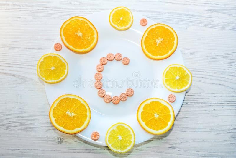 维生素C概念 药片和柑橘切片在板材 免版税图库摄影