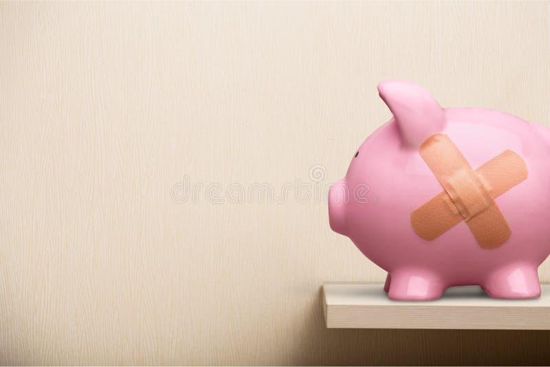 绷带的存钱罐在灰色背景 免版税库存图片