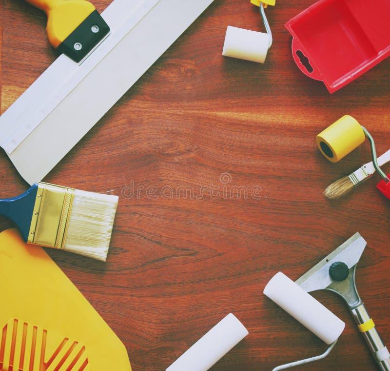 综合性刷子、泡沫路辗、小铲和其他工具为家庭修理在木背景 库存图片