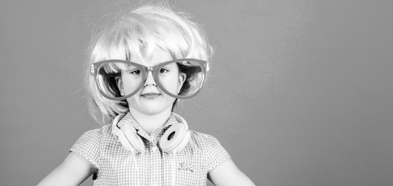 综合性头发 有桃红色头发假发的凉快的小孩 有花梢头发佩带的耳机的可爱的小女孩 免版税图库摄影