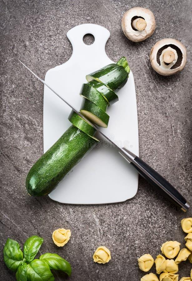 绿化在白色切板有厨刀的,顶视图的切的夏南瓜 吃健康的素食主义者烹调和,饮食食物 免版税库存图片