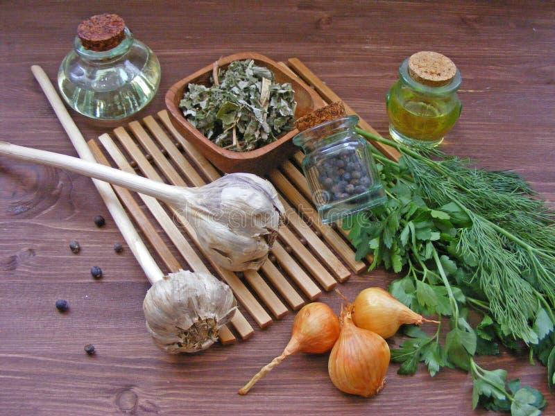 绿叶:新鲜的荷兰芹和莳萝、葱、大蒜、橄榄油在玻璃,干香料在碗和杜松子在木桌上 免版税库存照片
