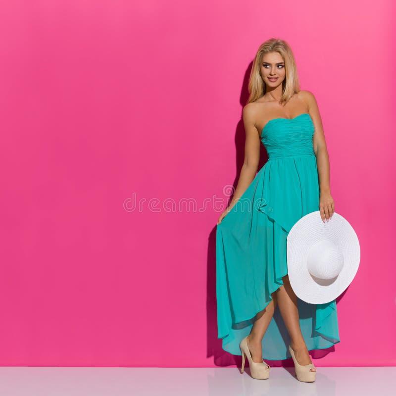 绿松石礼服和高跟鞋的美丽的白肤金发的妇女拿着白色太阳帽子并且看  库存图片