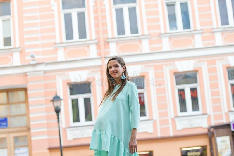 绿松石礼服的怀孕的女孩 天礼服的孕妇漫步在公园的 r 舒适的衣裳为 免版税库存图片