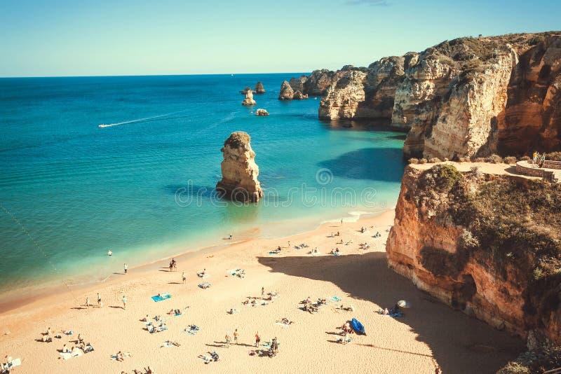 绿松石葡萄牙的海洋和海边 晴朗的海滩和镇静水的许多人在愉快拉各斯 图库摄影
