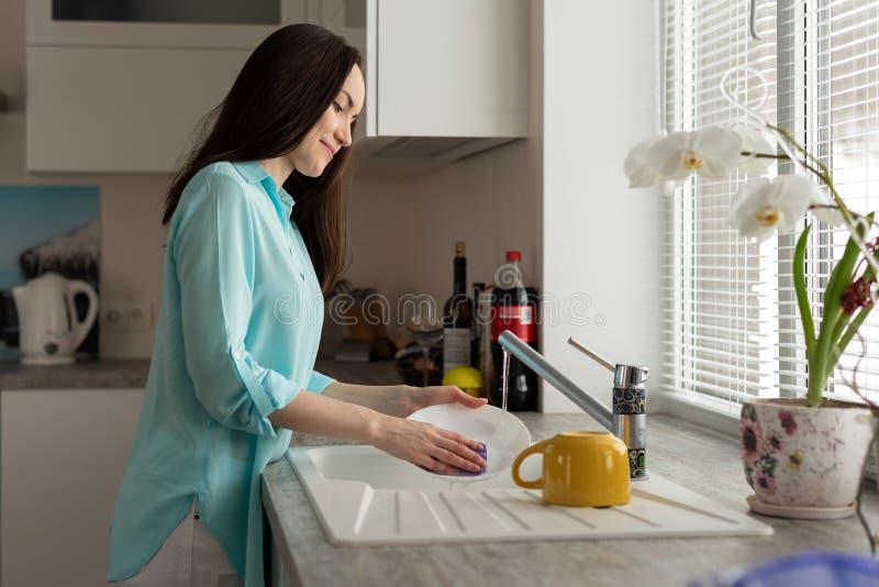 绿松石衬衣的一名妇女漂洗盘在轻拍下在厨房里 库存图片