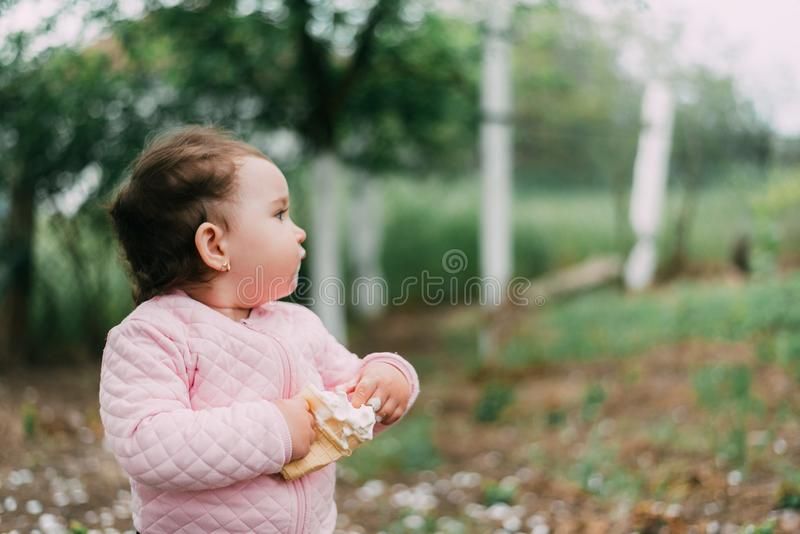 绿树背景的园中小女孩在华夫杯中吃冰激凌 免版税图库摄影
