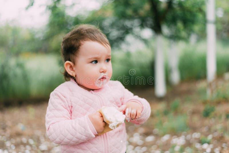 绿树背景的园中小女孩在华夫杯中吃冰激凌 库存图片