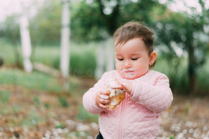 绿树背景的园中小女孩在华夫杯中吃冰激凌 免版税库存照片