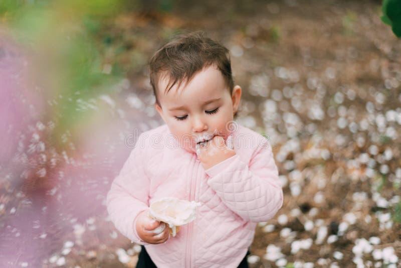 绿树背景的园中小女孩在华夫杯中吃冰激凌 免版税库存图片