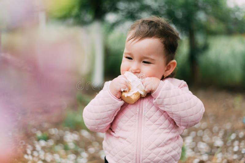 绿树背景的园中小女孩在华夫饼杯中吃冰淇淋很可爱 库存照片