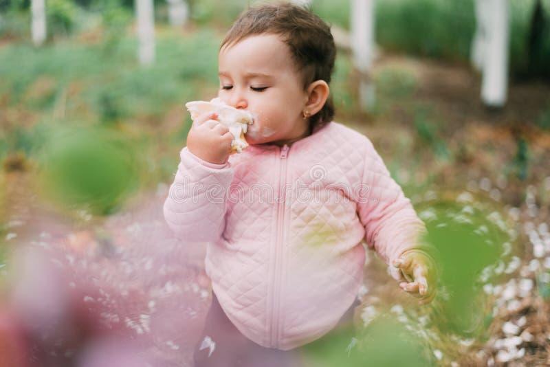 绿树背景的园中小女孩在华夫饼杯中吃冰淇淋很可爱 免版税库存图片