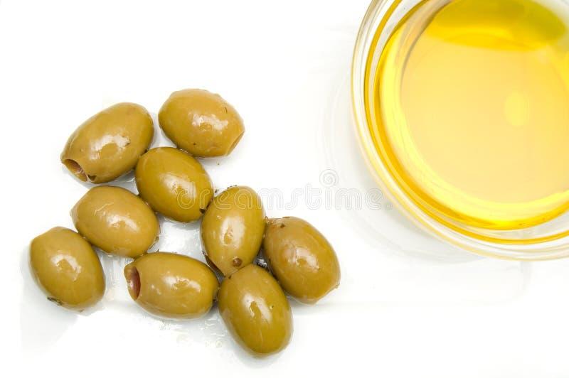 绿橄榄和碗在白色板材的橄榄油 免版税库存图片