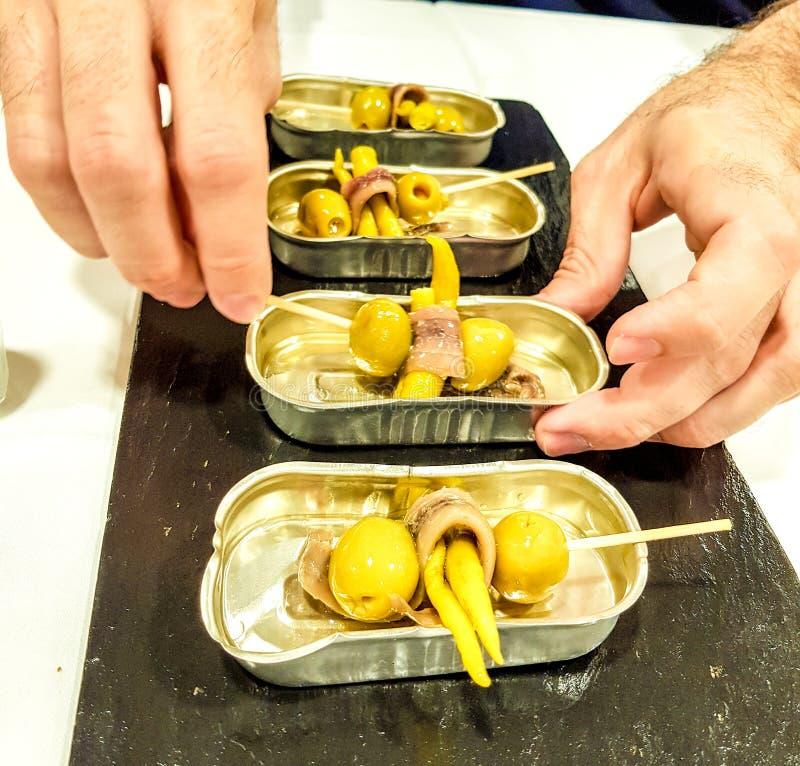 绿橄榄和辣椒点心在橄榄的金属盘子当前的Cantabrian鲥鱼包裹了和有手举行的 免版税库存照片