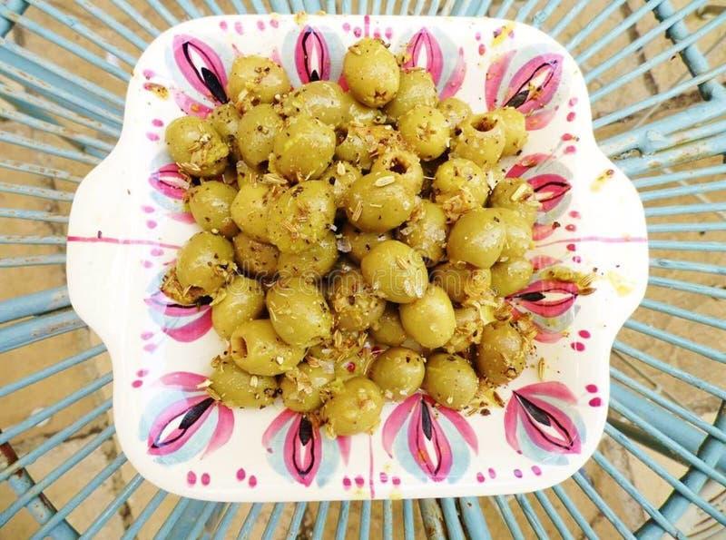 绿橄榄用卤汁泡与在葡萄酒盘的茴香籽 免版税库存照片