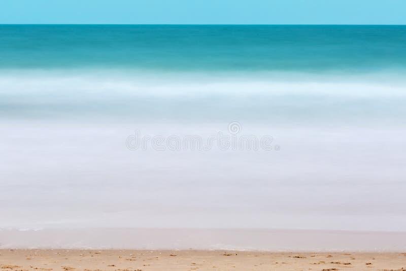 绿浪水流量表面和蓬松白色碎波采取与在海滩的长的曝光背景的 免版税库存图片