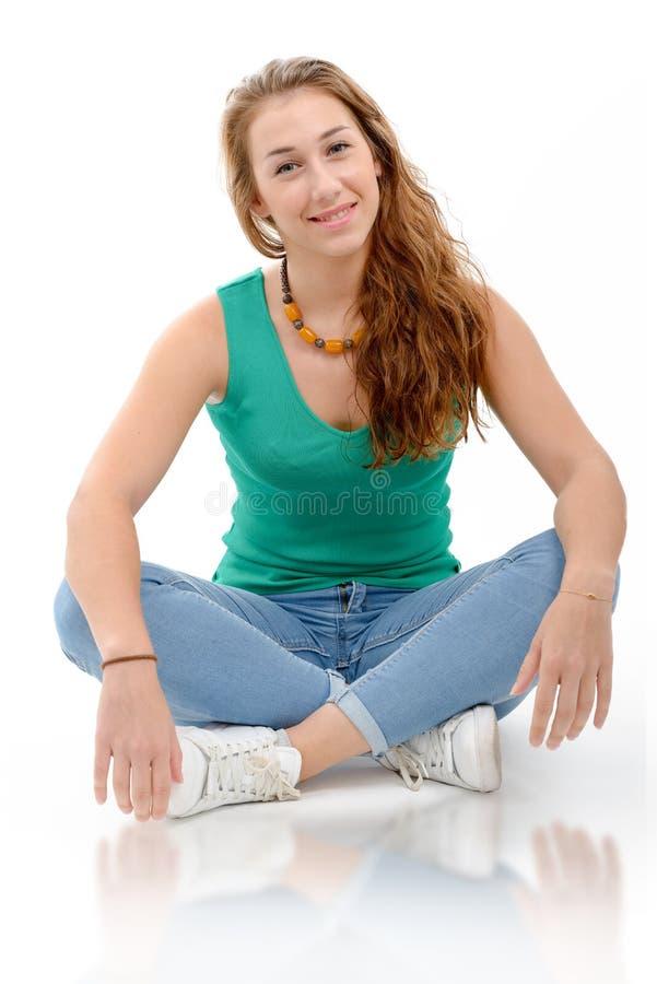 绿色偶然巧妙的衣物的,坐的横渡的l微笑的妇女 库存图片