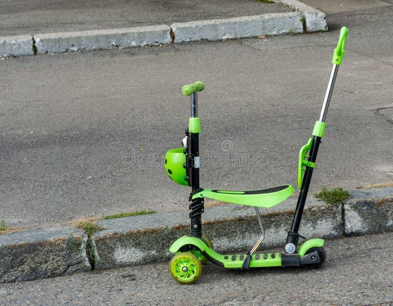 绿色儿童` s滑行车在街道天 免版税库存图片
