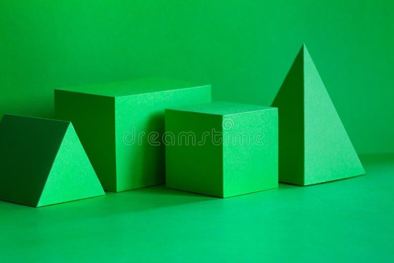绿色几何图静物画构成 三维在绿色的棱镜金字塔长方形立方体对象 库存图片