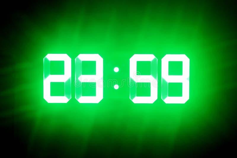 绿色发光的数字在黑暗的展示23:59 时间是一分钟对半夜12点 库存图片
