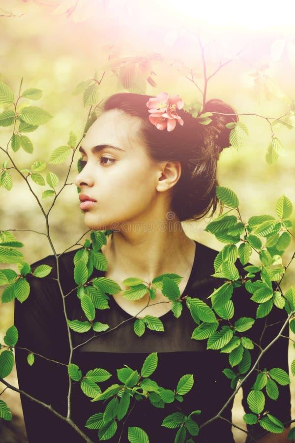 绿色叶子的妇女享受自然,在头发的红色花的 免版税库存图片