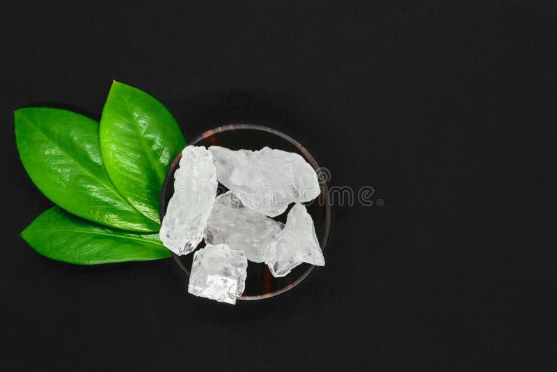绿色叶子的抽象构成、木黑暗的碗和大糖或者盐水晶在黑背景与拷贝空间 免版税库存照片
