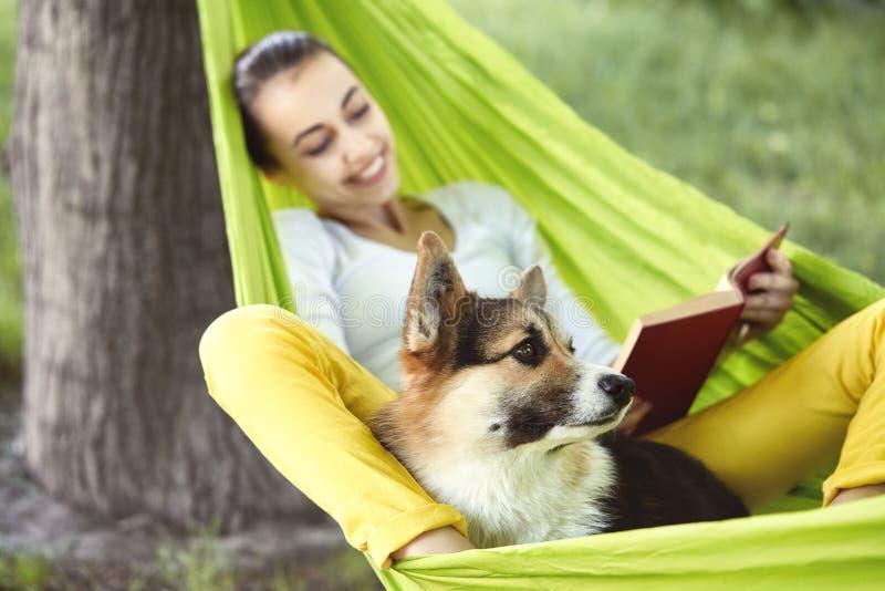 绿色吊床的微笑的年轻女人有滑稽的狗威尔士小狗的在公园户外 白色的美丽的愉快的女性 库存照片