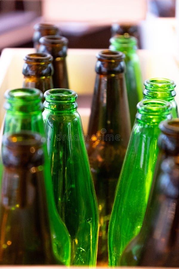 绿色和棕色玻璃瓶上面 许多空的玻璃瓶 减速火箭的形状的啤酒瓶优美的干净的玻璃纹理  图库摄影
